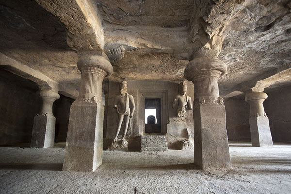 View of the main cave with two guardians sculpted out at a lingam shrine in the background | Grutas de Elefanta | India