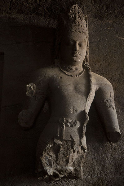 Remains of a sculpture of a dvarapala, a doorkeeper, at the entrance of a linga shrine in the main cave | Grutas de Elefanta | India