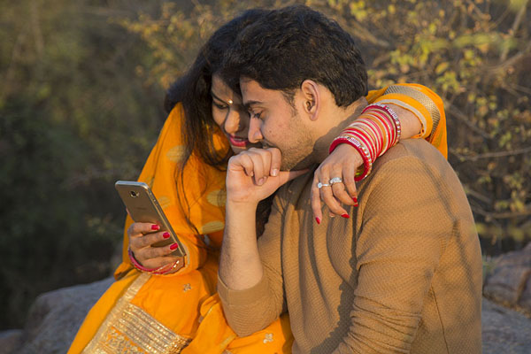 Picture of Indian couple with a golden smartphone in the Garden of Five Senses