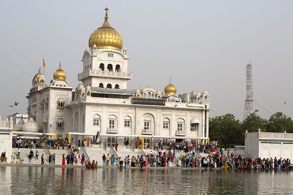 Picture of People congregating at the sarovar, or square pool, with Gurudwara Bangla Sahib
