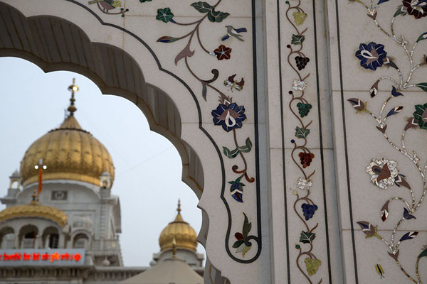 The inlaid arched entrance witht the golden dome of Gurudwara Bangla Sahib in the background德里 - 印度