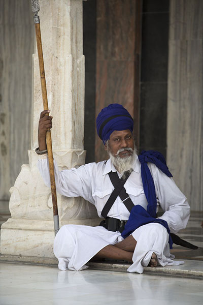 Foto van Sikh with long wooden stick with metal point at Gurudwara Bangla SahibDelhi - India