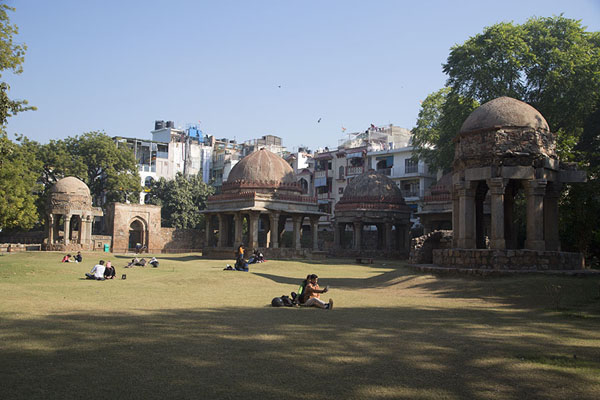 People sitting in the gardens of the madrasa with chhattris, tombs of the Tughlaq period | Hauz Khas | India