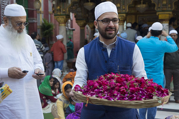 Foto van Man with basket full of flowers for offering at the Nizamuddin Auliya shrineDelhi - India