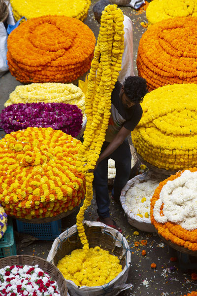 Foto de Man rearranging a yellow garland at KR marketBengaluru - India