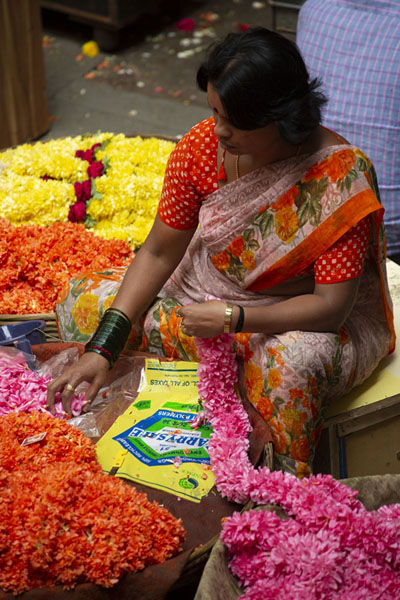 Foto de Woman arranging flowers at her market stallBengaluru - India