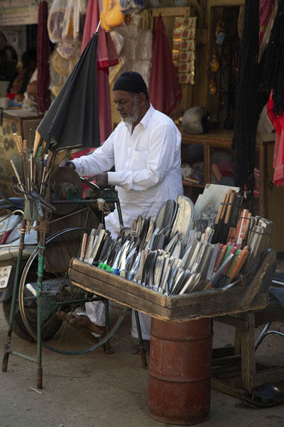 Man sharpening knives at one of the many street stalls of KR market | Krishnarajendra markt | India