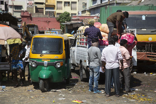 People unloading a truck at the side of the main market building | Mercato Krishnarajendra | India