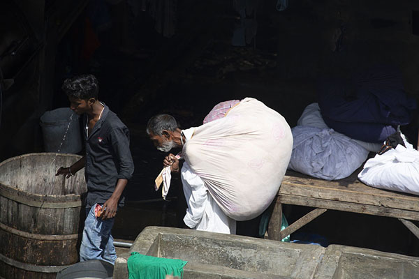 Man carrying a heavy load of laundry to be washed at Dhobi Ghat | Mahalaxmi Dhobi Ghat | Inde