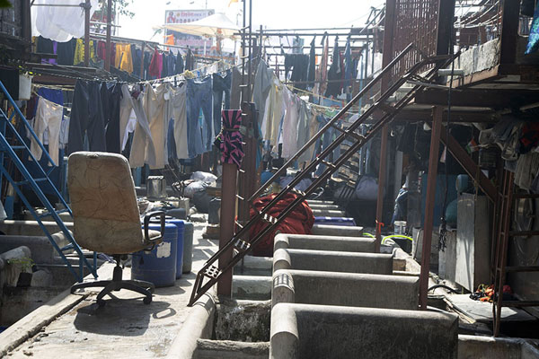 Concrete washing pens, a chair, stairs, and laundry | Mahalaxmi Dhobi Ghat | India