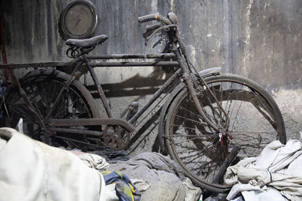 Picture of Old dusty bike parked against a wall in a dark corner of Dhobi GhatMumbai - India