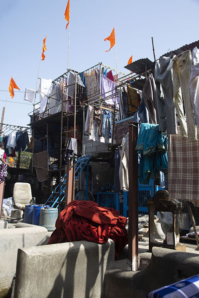 Looking up into the sky from below, with clothes hanging to dry topped with orange flags | Mahalaxmi Dhobi Ghat | India