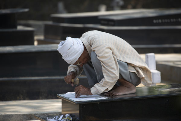 Old Indian man engraving a text in a marble tombstone | Cimitero Nicholso | India