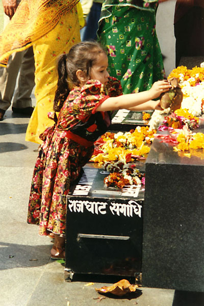 Foto van Young Indian girl laying flowers on the black marble memorial of Mahatma Gandhi - India - Azië