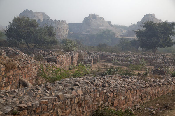 Crumbling wall with the defensive towers of Tughlaqabad Fort in the background | Tughlaqabad Fort | India
