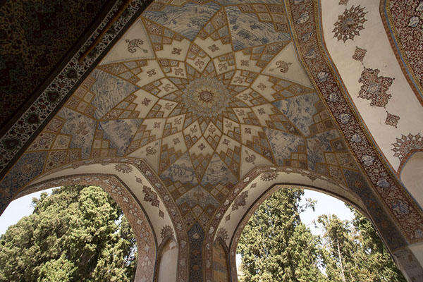The ceiling of a pavilion with trees behind in Fin Garden | Fin Garden | Iran