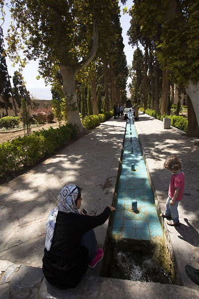 Mother with child at one of the canals running through Fin Garden | Jardines de Fin | Irán