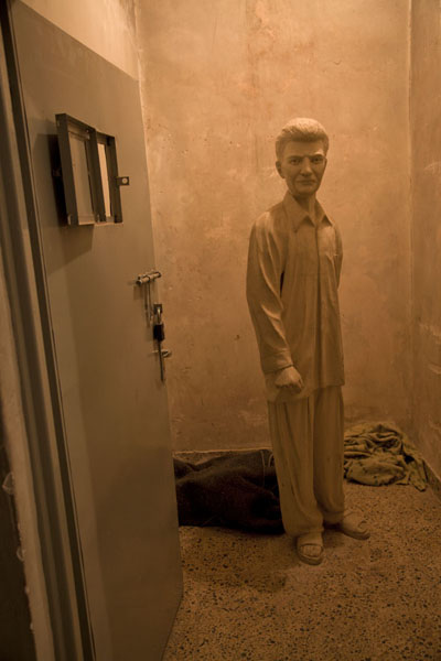 One of the cells of Amna Suraka with a sculpted prisoner | Amna Suraka prison | Iraq