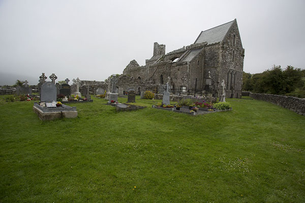 Picture of Corcomroe Abbey (Ireland): Cemetery with the church of Corcomroe Abbey in the background