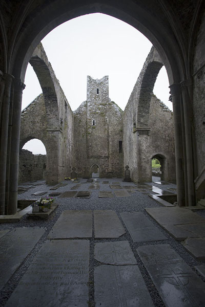 Looking through an arch of Corcomroe Abbey with tombstones on the floor | Corcomroe Abbey | Ireland