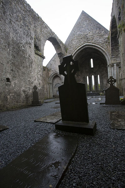 Foto van The main aisle of Corcomroe Abbey church with tombstones - Ierland - Europa