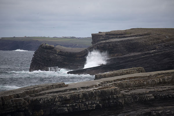 Waves crashing on the rugged black layered rocks near the Bridges of Ross | Loop Head Schiereiland | Ierland