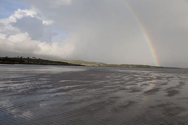 Foto van Rainbow over the exposed land at low tide between the mainland and Omey IslandOmey Island - Ierland