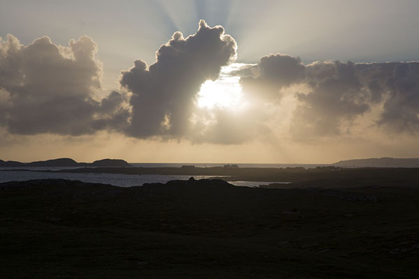Foto di Sun shining through the clouds over Omey IslandOmey Island - Irlanda