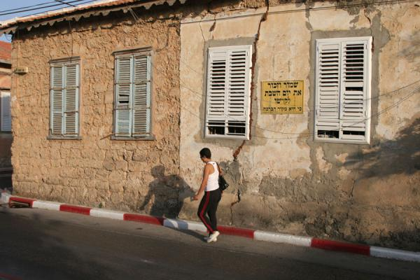 Photo de Woman walking down a street in Neve TzedekTel Aviv - Israël