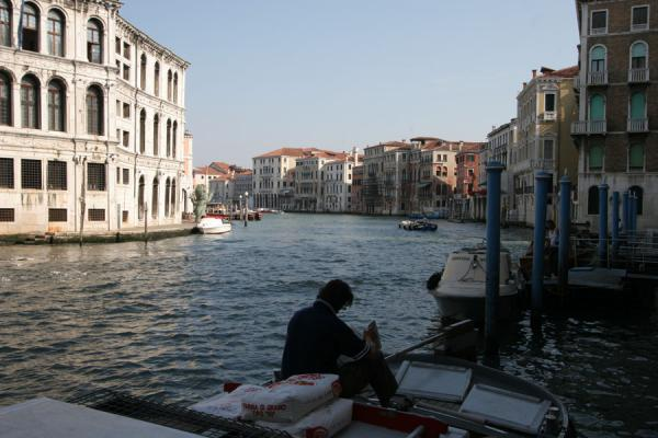 Reading a newspaper on a boat on Canal Grande | Canal Grande | Italy
