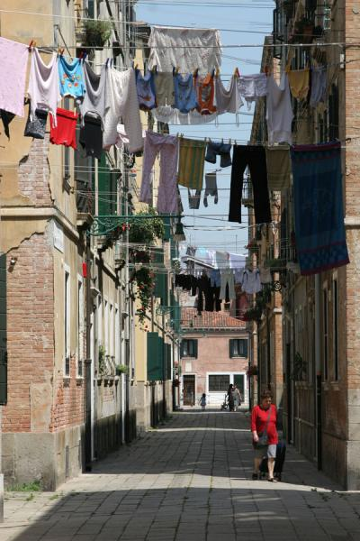 Woman in red walking a street with laundry | Castello | Italy