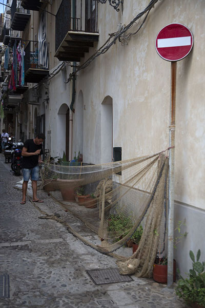 Picture of Street in Cefalù with fisherman working on his net using a traffic sign - Italy - Europe