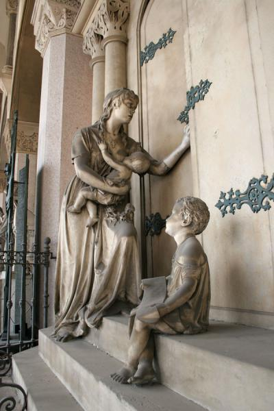 Sculptures of woman and child seemingly entering a tomb | Monumental Cemetery | Italy