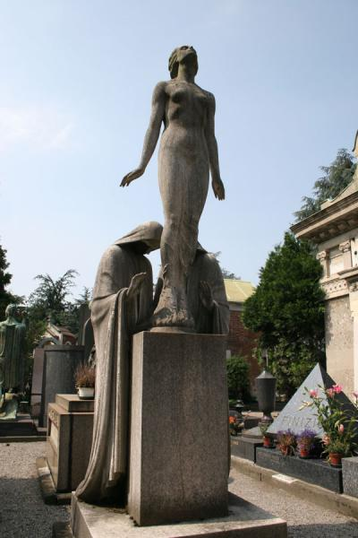 Woman towering high above tomb in Cimitero Monumentale | Monumental Cemetery | Italy