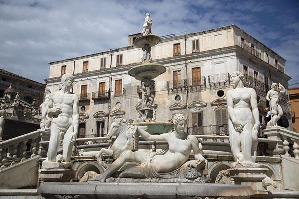 Foto van The statues of the Fontana Pretoria in plain sunlight with the Palazzo Guggino Bordonaro in the backgroundPalermo - Italië