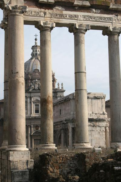 Columns of the Temple of Saturn with church in the background | Forum Romanum | Italy