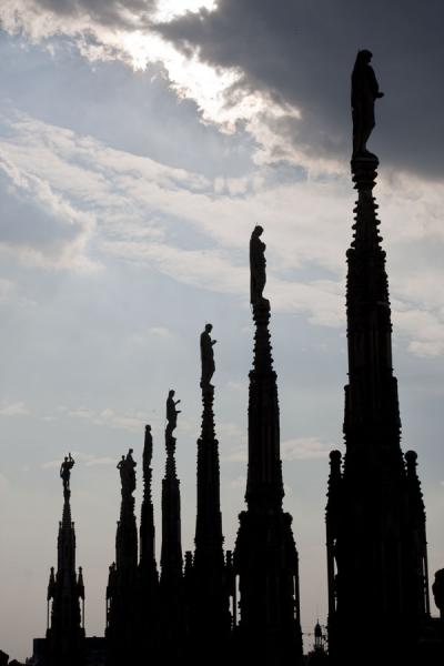Picture of Milan Cathedral (Italy): Spires and status silhouetted against the afternoon sun on the roof of Milan Cathedral