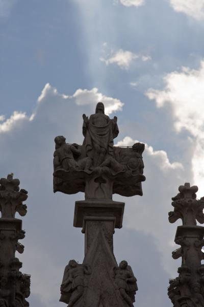 Foto de Cross-shaped decoration with religious figures on top of the roof of the cathedralMilán - Italia