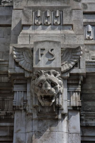 Foto van Detail of the exterior of the central station with lion head and the emblem of Italian Railways, FSMilaan - Italië