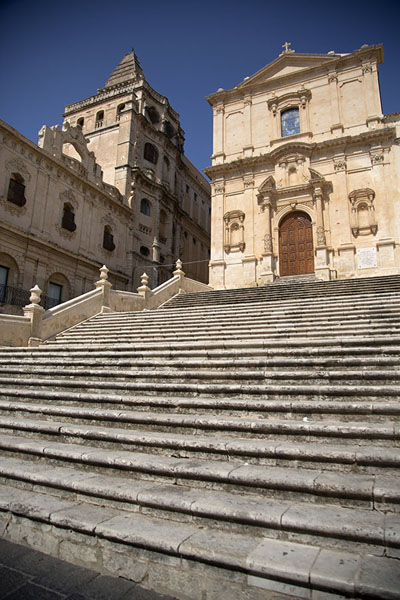 Looking up the steps of the Chiesa di San Francesco d'Assissi all'Immacolata and monastery on the left | Noto | Italy