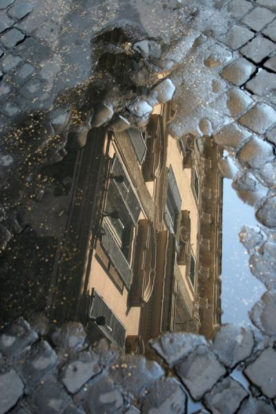 Reflection of houses in a pool of rainwater in the streets of Pigna | Pigna | Italy