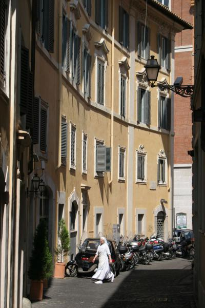 Nun walking past motorcycles in quiet street in Pigna, Rome | Pigna | Italy