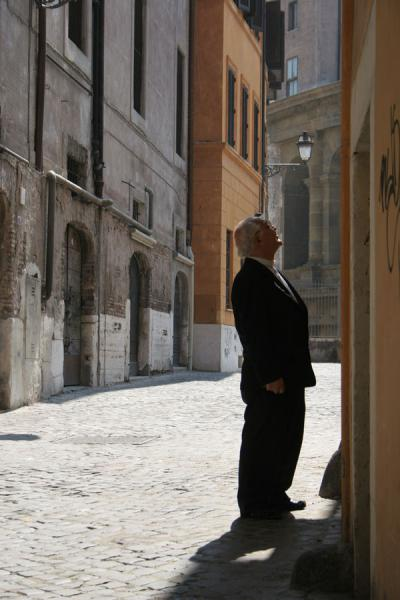 Picture of Pigna (Italy): Old man looking at a poster in the street in Pigna district, Rome