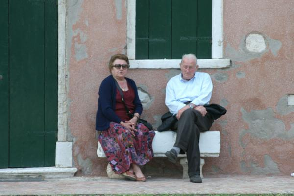 Two old people chatting on bench of main square in Torcello | Torcello | Italy