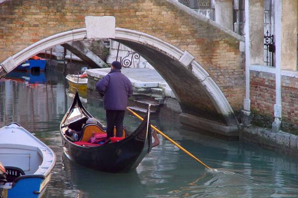 Gondolier under a bridge | Venetian canals | Italy