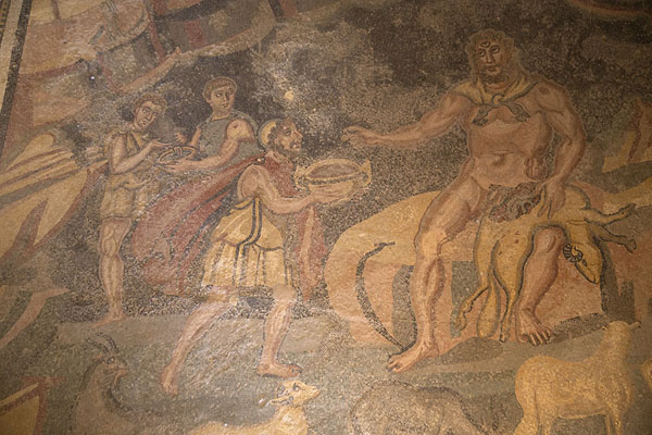 Polyphemos, the cyclops depicted with three eyes here, receiving a cup of wine from Odysseus | Villa Romana del Casale | Italië
