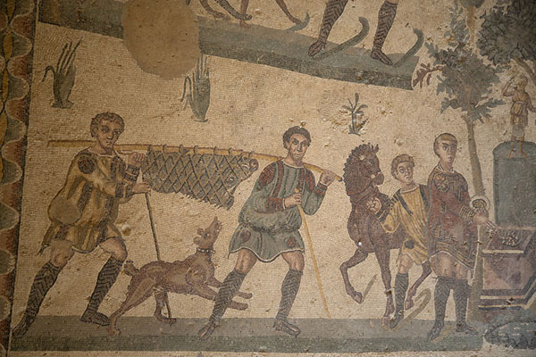 Close-up of a hunting scene: man carrying a caught pig, a hunting dog, and men with a horse | Villa Romana del Casale | Italy