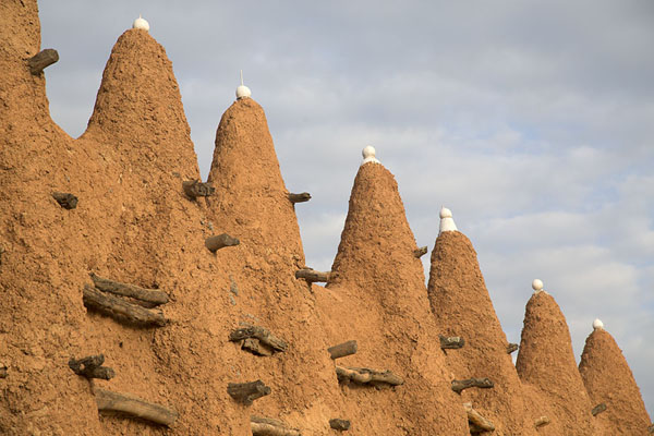 Crenellated wall with fake ostrich eggs at the mosque of Kong | Kong mosque | Ivory Coast