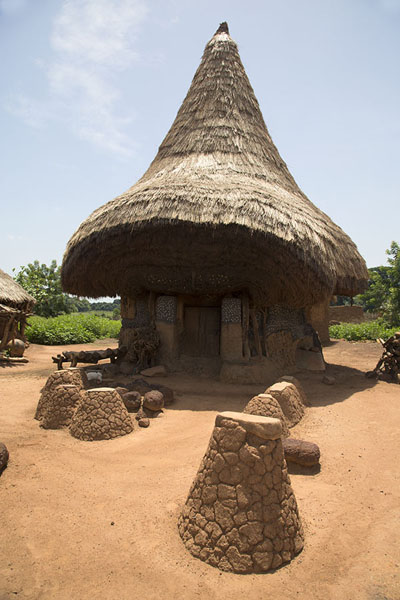 Picture of Niofoin (Ivory Coast): The house of Diby with thick, thatched roof and special platforms to put masks which are not supposed to touch the ground