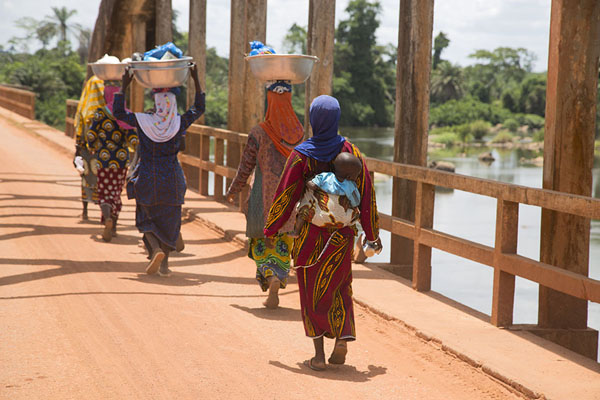 Women walking the bridge with their wares | Pont Weygand | Ivory Coast